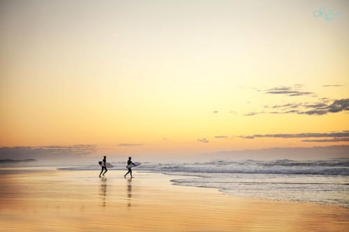 Dawn surfers hurry to the ocean.